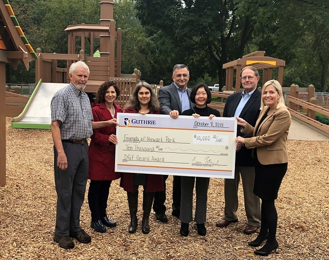 People holding large check on playground