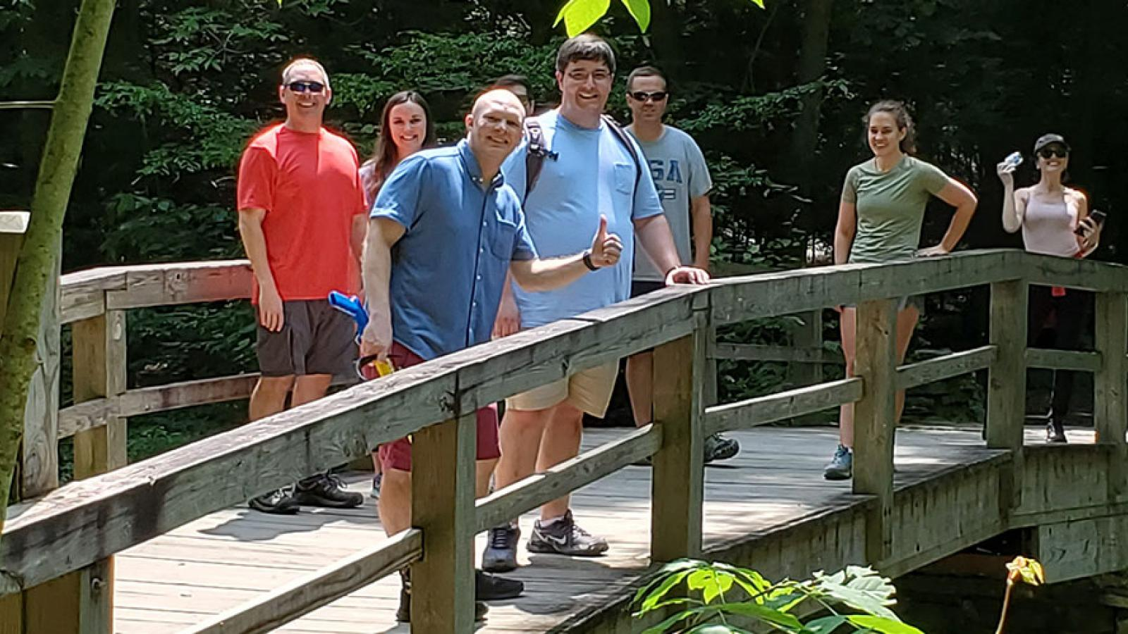 People standing on a bridge in the woods